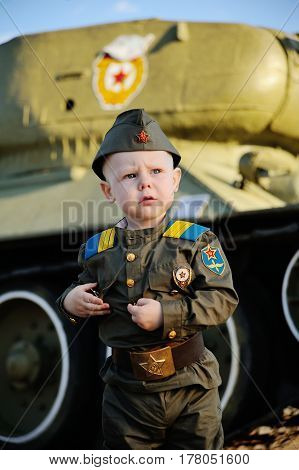 Baby boy in military uniform on tank background. May 9, World War II, defender, February 23.