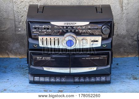 Cassette Tape Recorder With Radio On A Blue Wooden Table. Vintag