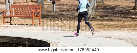 A women is running around Belmont Lake on a cool spring morning