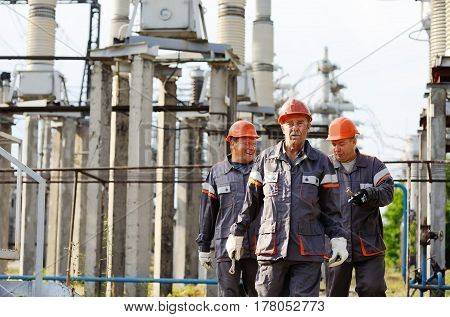Working with a tool in the hands against the background of power plant.Repair team of electricians against the background of a power station