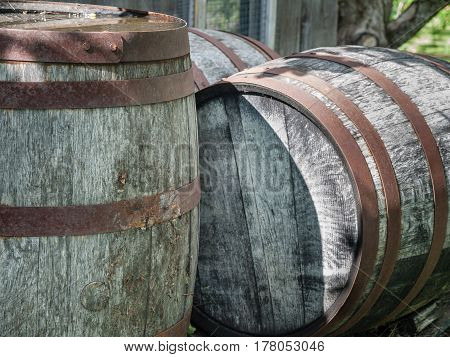 Old rusted wine barrels outside with one laying dow