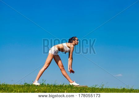 Young slim woman exercising in the park on a background of blue sky