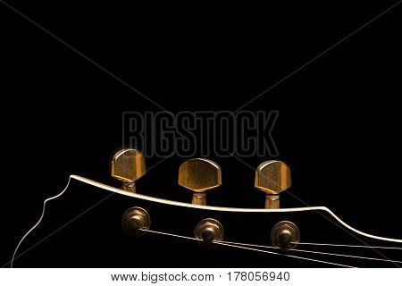 Black guitar's headstock on ottom of image with gold tuning posts on black background