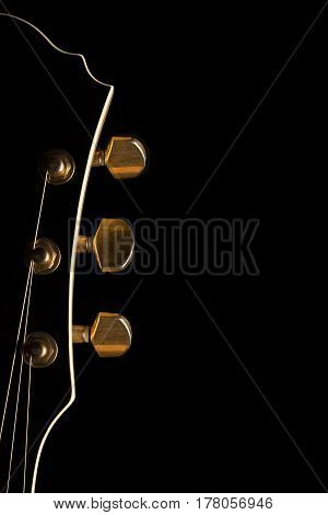 Black guitar's headstock on left side of image with gold tuning posts on black background