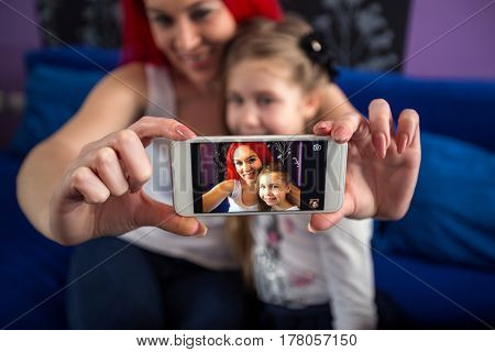 Taking photo with mobile phone mom and daughter having fun