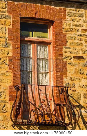 Brick Window with lace curtains on an old stone building