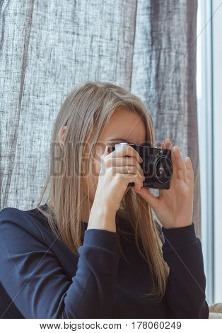 Pretty girl photographer with vintage retro camera making pictures.
