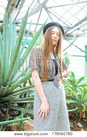 Young fashionable caucasian woman with long hair wearing hat and striped blouse basking in sunlight inside greenhouse near agava plants