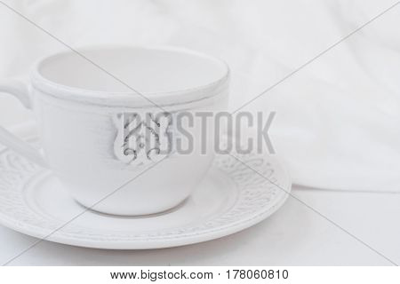 White relief ceramic tea cup with saucer on wood table cotton fabric purity concept minimalist styled image for social media banner header