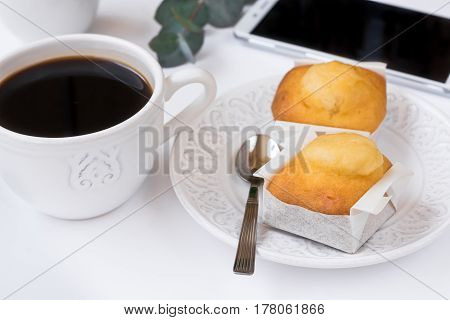 White cup with coffee smartphone pastry on plate eucalyptus branch on table business breakfast feminine styled image for blogging social media