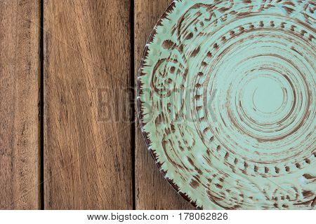 Empty vintage blue plate with ornament on wood table top view flat lay styled photo for menu marketing website header banner