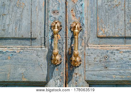 Vintage antique door handle on the old blue wooden door.