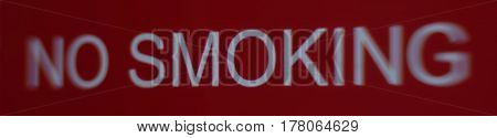 A fairly distorted red no smoking sign