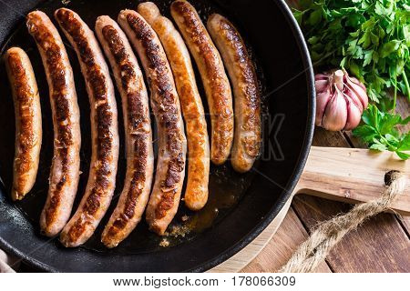 Fried sausages with golden crust in iron cast pan garlic and fresh parsley on wood kitchen table top view cooking concept cozy atmosphere