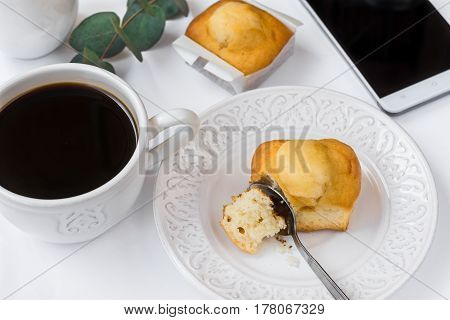 Top view of white table surface cup of coffee pastry on plate smartphone eucalyptus branch styled image for social media female business cozy breakfast atmosphere
