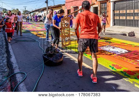 Antigua, Guatemala - March 19 2017: Locals make Lent carpets of dyed sawdust using stencils in path of religious procession in colonial town with most famous Holy Week celebrations in Latin America.
