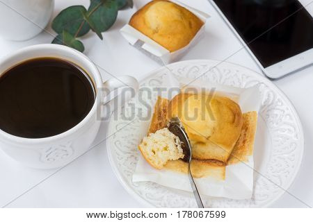 Top view of white table surface cup of coffee muffin on plate smartphone eucalyptus branch styled image for social media cozy breakfast atmosphere business