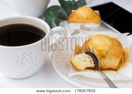 Cup of coffee pastry on plate smartphone eucalyptus branch on white table feminine business style image for social media