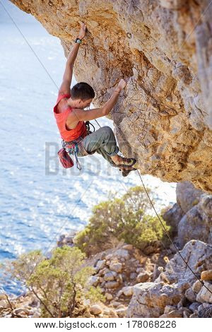 Young man lead climbing on overhanging cliff on coast Kalymnos island Greece