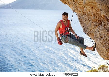 Male rock climber resting while hanging on rope before next attempt on challenging route