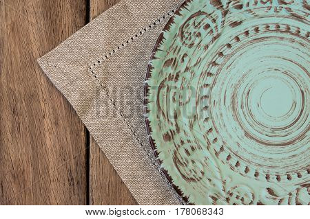Empty vintage relief plate on linen napkin on plank wood table top view flat lay mockup menu template product marketing styled image
