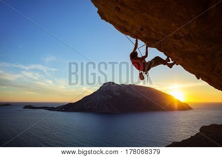 Young man climbing overhanging cliff at sunset Kalymnos island Greece. Beautiful evening view of Telendos island in background.