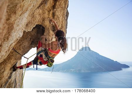 Young woman struggling to climb ledge on cliff against view of sea and island