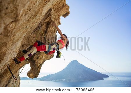 Young woman struggling to climb overhanging cliff against view of sea and island poster