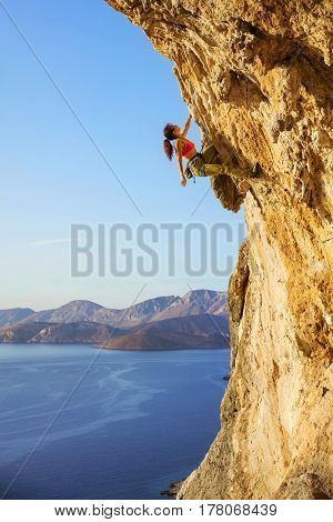 Female rock climber on challenging route looking up at cliff view of coast below