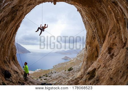 Rock climbers in cave: leading climber flexing muscles jokingly his partner belaying