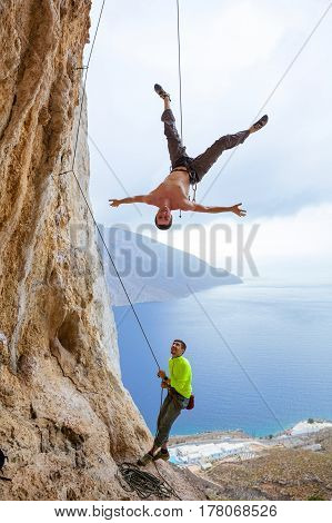 Rock climbers fooling around: one man hanging upside down while being lowered belayer watching him and smiling