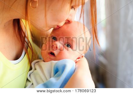 Portrait of happy mother and baby together at home