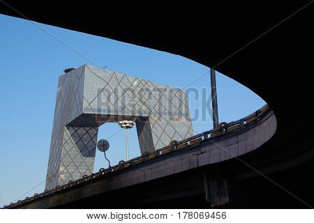 Low angle look up the bridge behind the building background is CCTV Tower of BeijingChina .