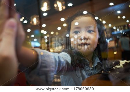 Asian father and cute little girl saying goodbye through the glass window .