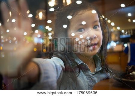 Little asian girl saying goodbye through the glass window .