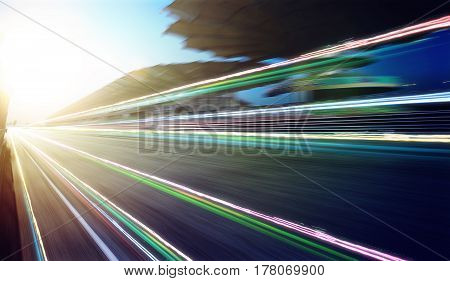 Foward motion speed lens blur racing circuit background with seated stand sunset scene and light trail effect .