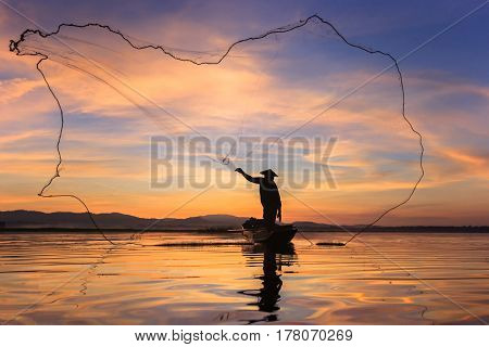 Silhouette fisherman on fishing boat setting net with sunrise