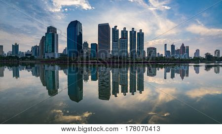 Sunrise scence of Bangkok Panorama Aerial view of Bangkok modern office buildings and condominium in Bangkok city downtown with sunrise sky and clouds at Bangkok Thailand. And Reflection on Lake.