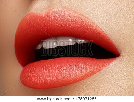 Cosmetics makeup and trends. Bright lip gloss and lipstick on lips. Closeup of beautiful female mouth with red and pink lip makeup. Beautiful part of female face. Perfect clean skin
