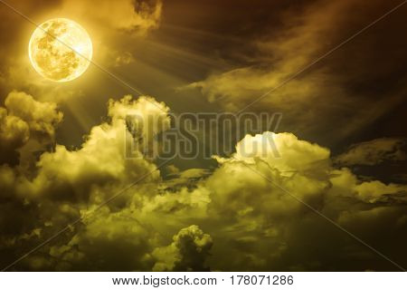 Night sky with cloudy and bright full moon over yellow nature background.