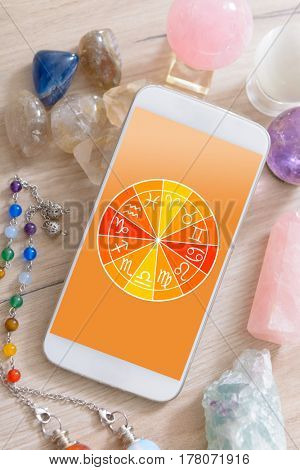 Zodiac signs and smart phone with crystals. Concept of modern astrology.