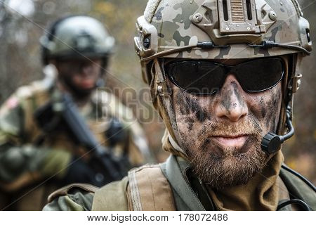 Norwegian Armed Forces Special Command FSK male and female soldiers closeup portrait. Radio and headset are on. Foreground blurred