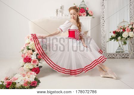 A sweet ballerina in a scenic suit next to bouquets of spring flowers. Retro dress.