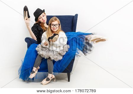 The elder sister and little girl ballerina are sitting in a chair. They keep their shoes on high heels. Girls in ballet tutu and pointe shoes. Lovely girl. Family tradition