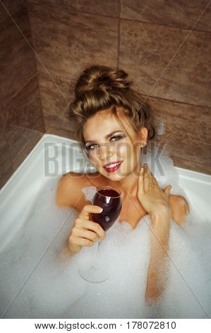 Young cute girl drinking red wine in bath with foam. She relaxes after a hard day. Girl coquettishly looking up and stroked her neck.