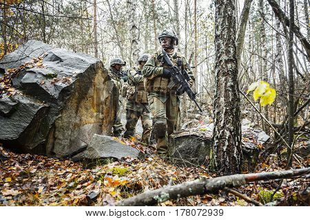 Norwegian Rapid reaction special forces FSK male and female soldiers in field uniforms patrolling in the forest trees