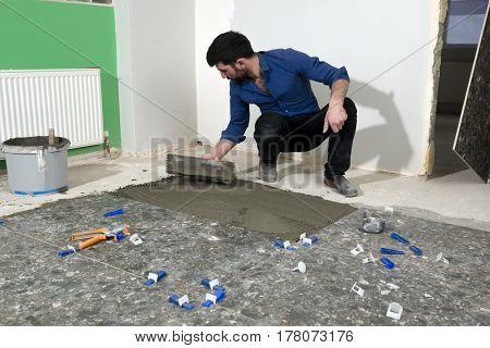 Real Worker Applying Ceramic Glue
