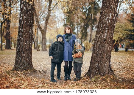 two boys standing in the park with her mother
