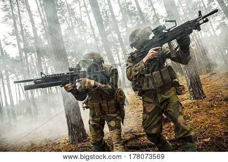 Norwegian Rapid reaction special forces FSK soldiers in field uniforms in action in the forest fog covering each other, cropped