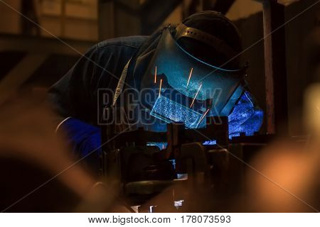 Welder with protective mask  is welding steel in factory